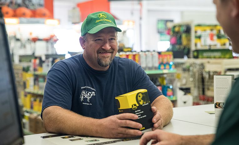 man in John Deere hat at parts counter