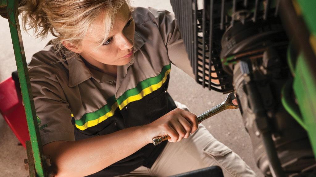 woman doing maintenance work on a piece of Deere equipment
